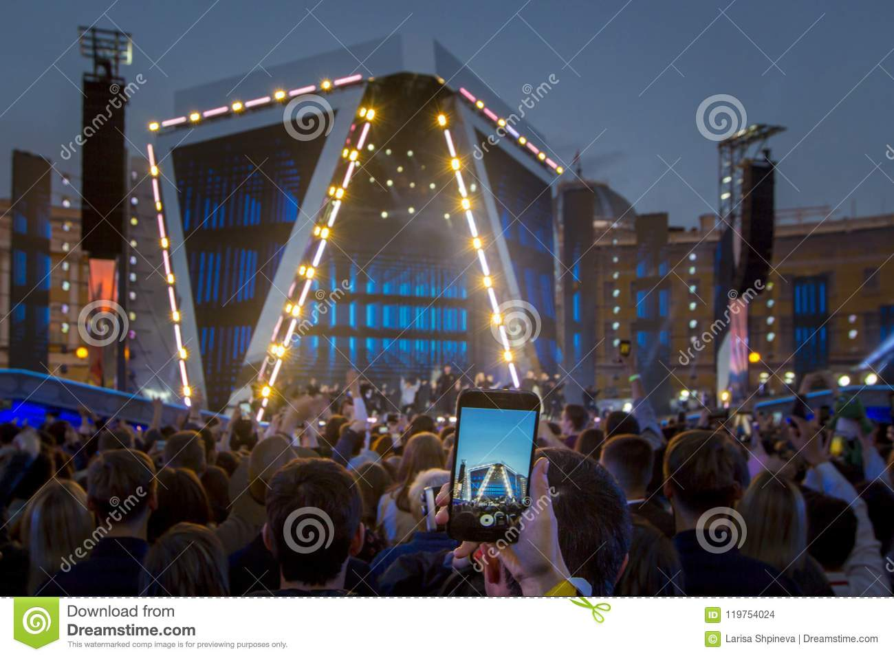 Hand with smartphone recording video / photo at live music concert, silhouettes of crowd in front of bright stage lights.