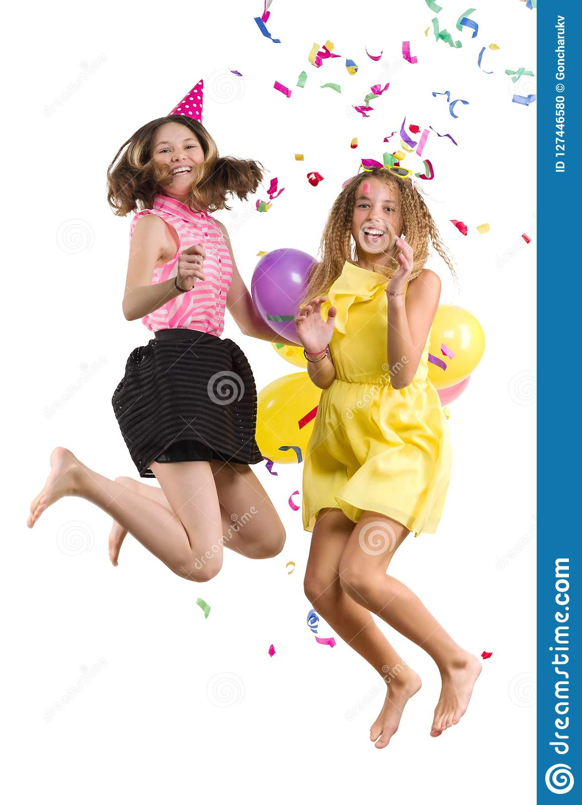 Party of teenage girls, girls with balloons, confetti in festive hats having fun, children are jumping, white background is isolat