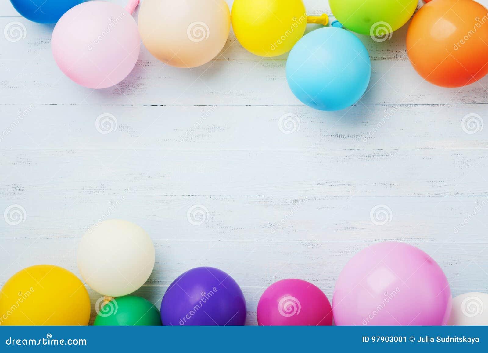 Partyjny lub urodzinowy sztandar z kolorowymi balonami na błękitnego drewnianego tła odgórnym widoku mieszkanie nieatutowy styl