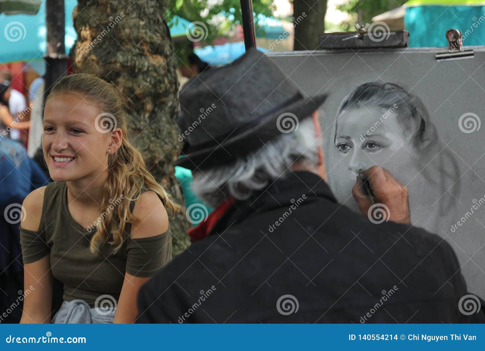 Paryż Francja, Sierpień, - 27,2017: Artysta jest rysunkowym portretem dla dziewczyny na ulicie