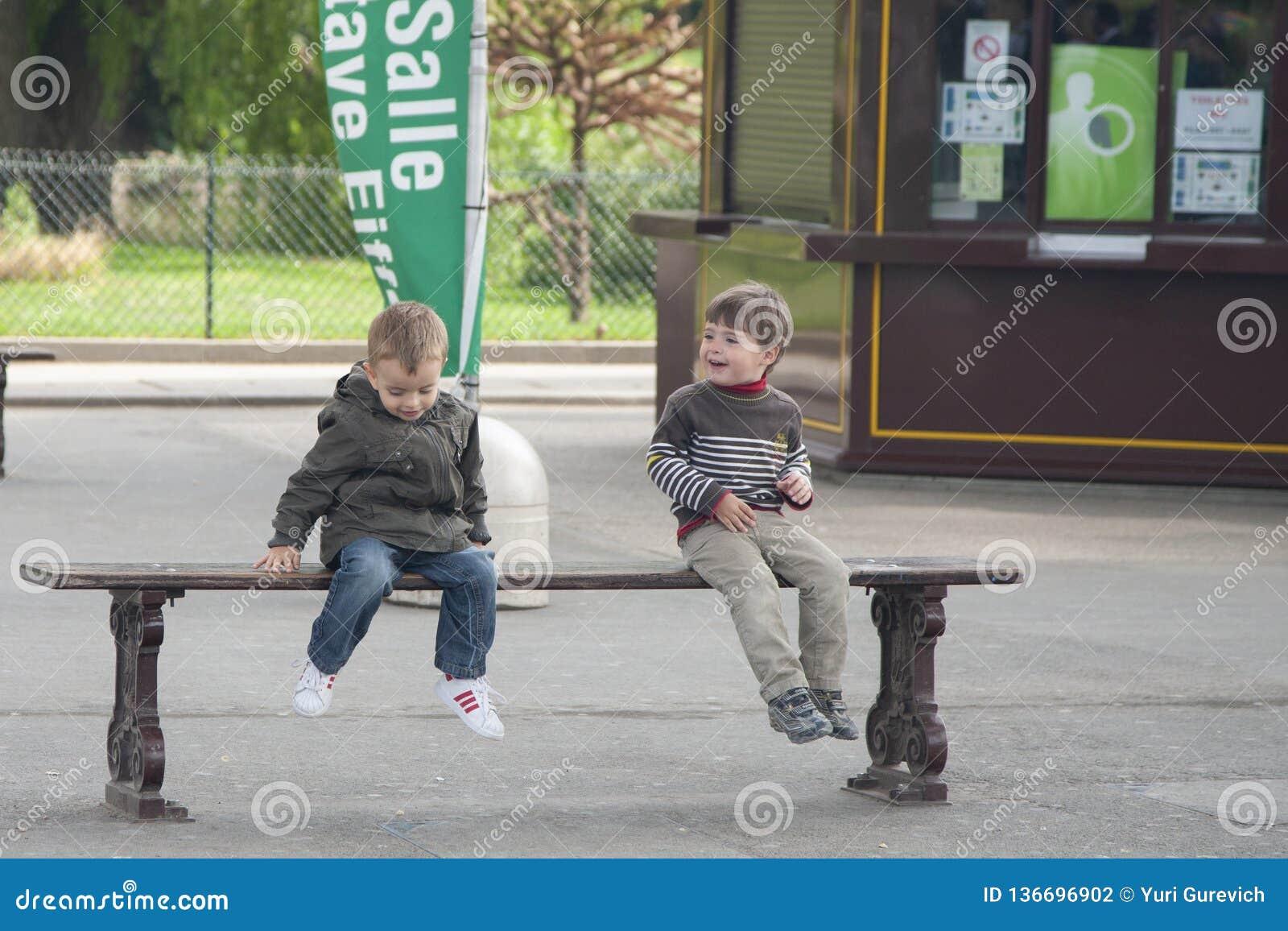 Paryż Francja, Kwiecień, - 12, 2011: Chłopiec siedzą na opowiadać i ławce