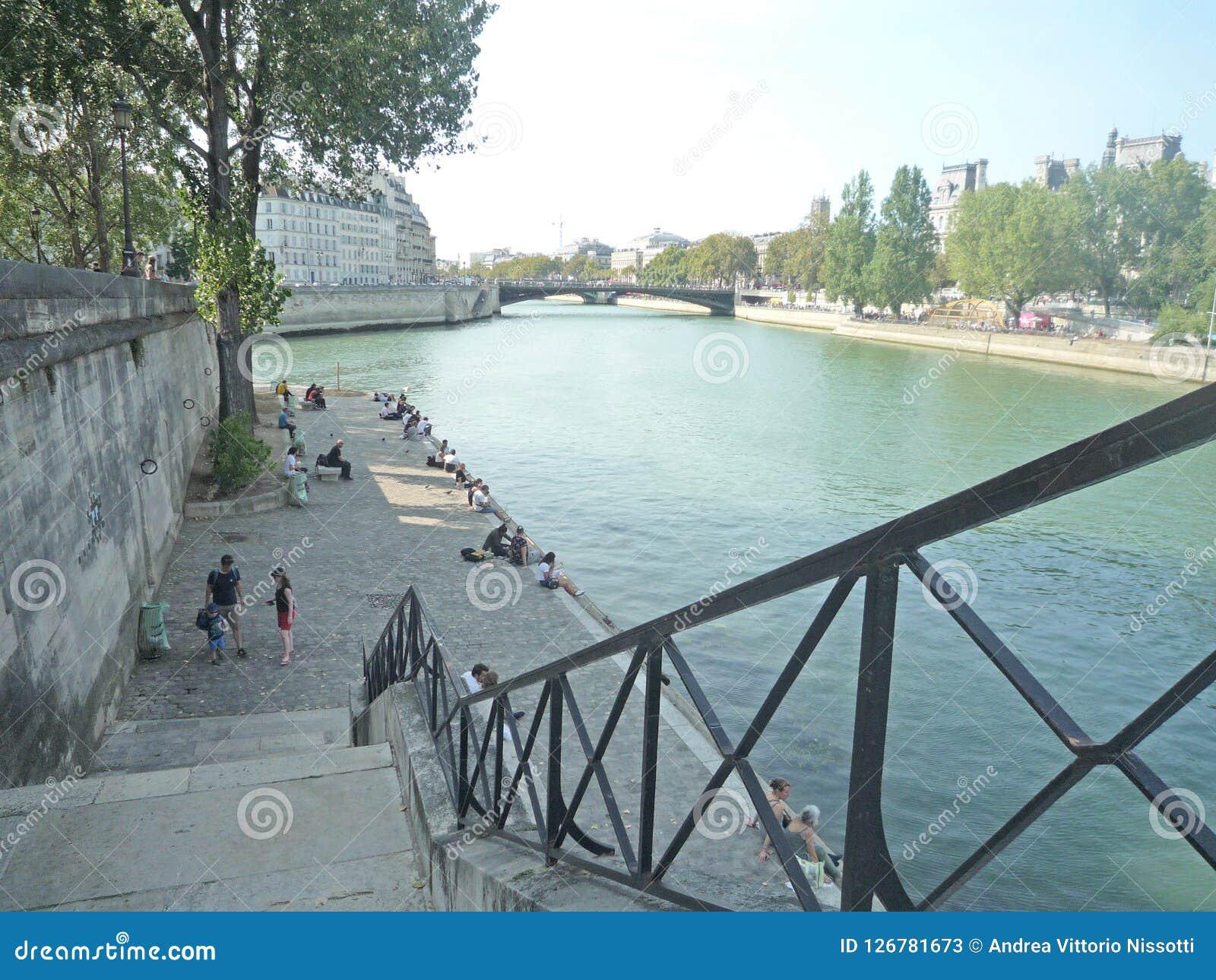 Paryż, Francja, Sierpień 18 2018: ludzie siedzi i chodzi wzdłuż rzeki strony