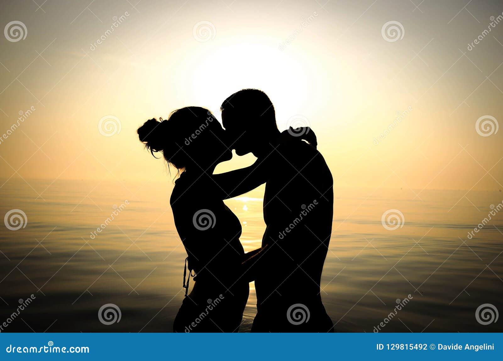 Pary całowanie przy plażą przy zmierzchem