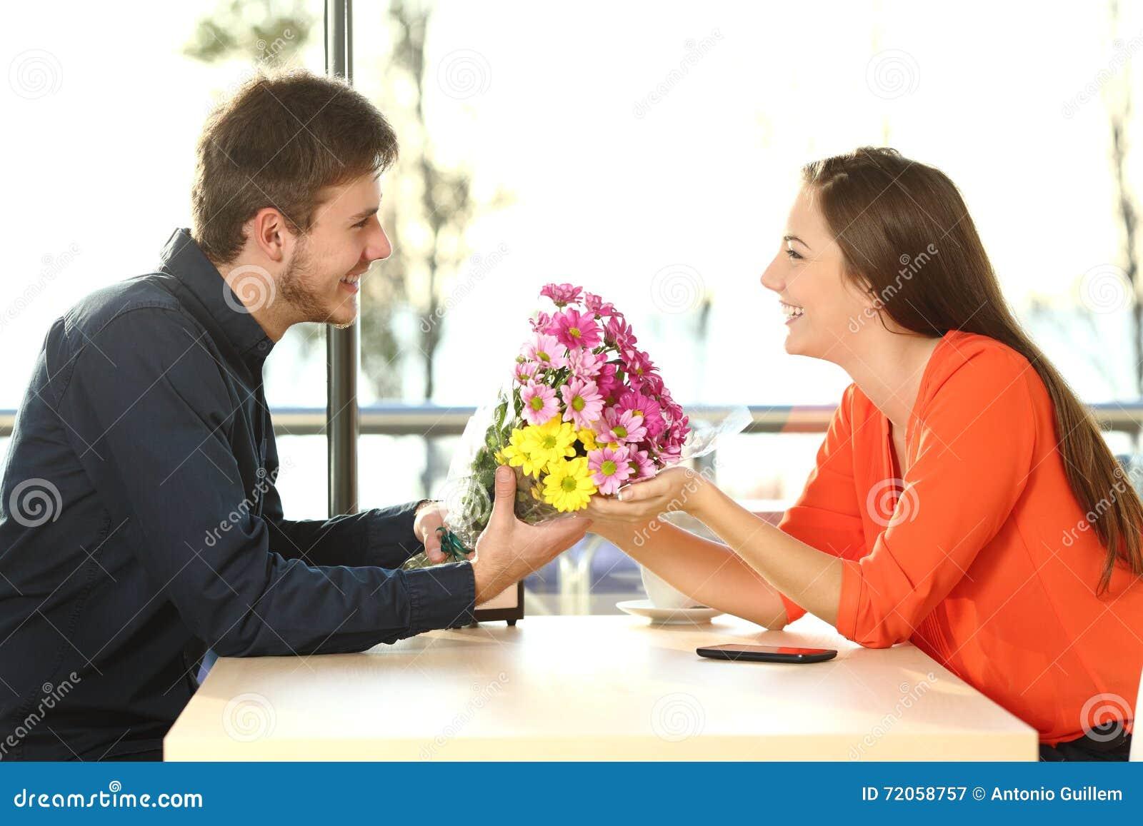 Pary data z mężczyzna daje kwiaty