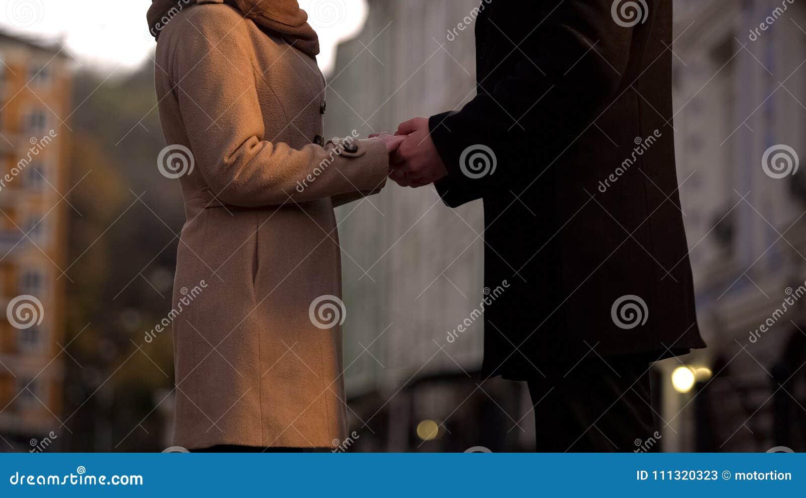 Pary małżeńskiej mienie wręcza tenderly w miłości, wciąż, romantycznego spacer w dużym mieście