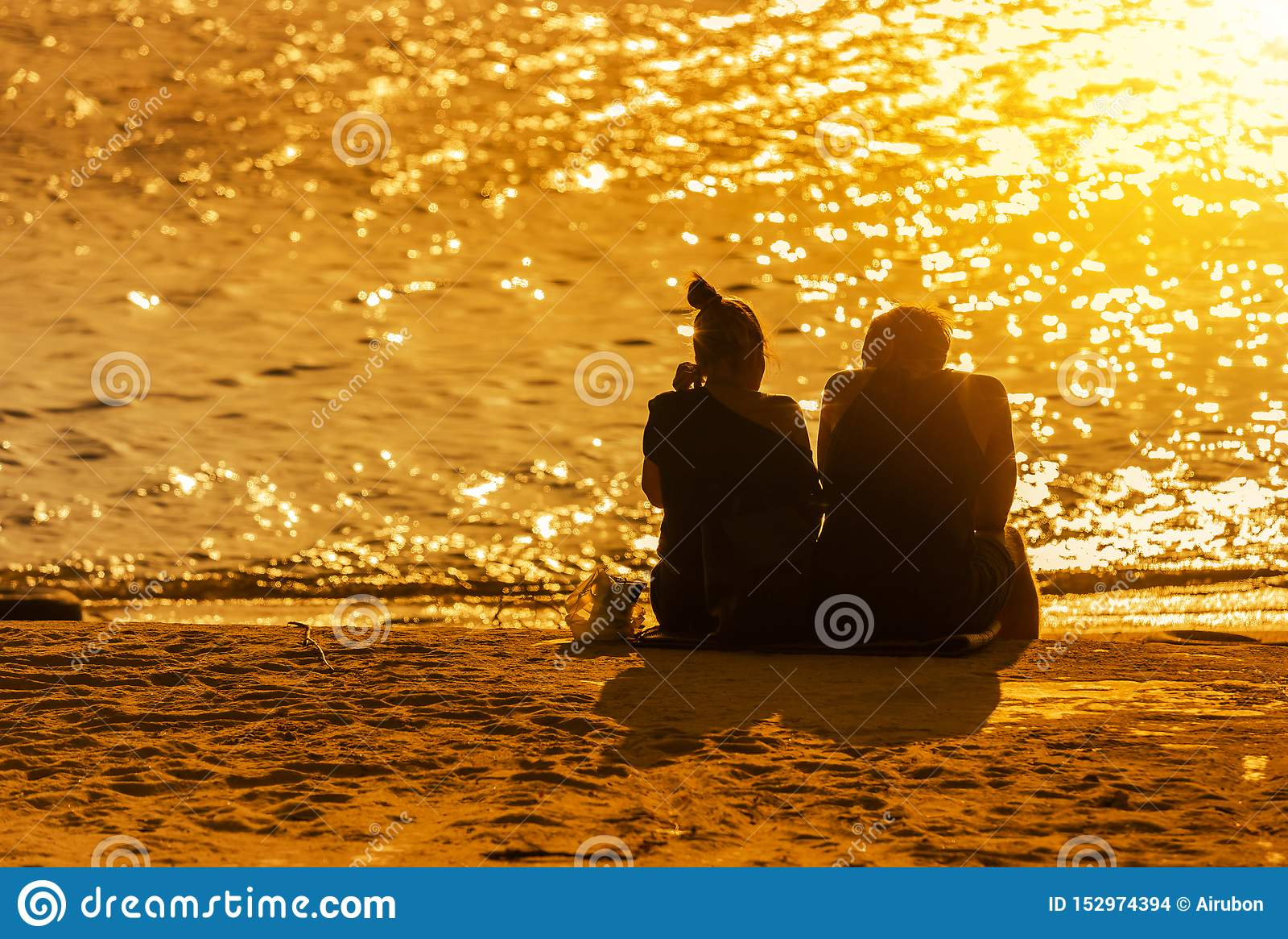 Pary miłość siedzi relaksować na tropikalnej plaży podczas zmierzchu czasu