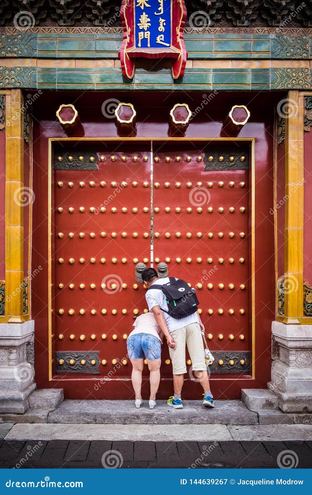Pary zerkanie przez małego otwarcia w drzwi przy Niedozwolonym miastem w Pekin Chiny