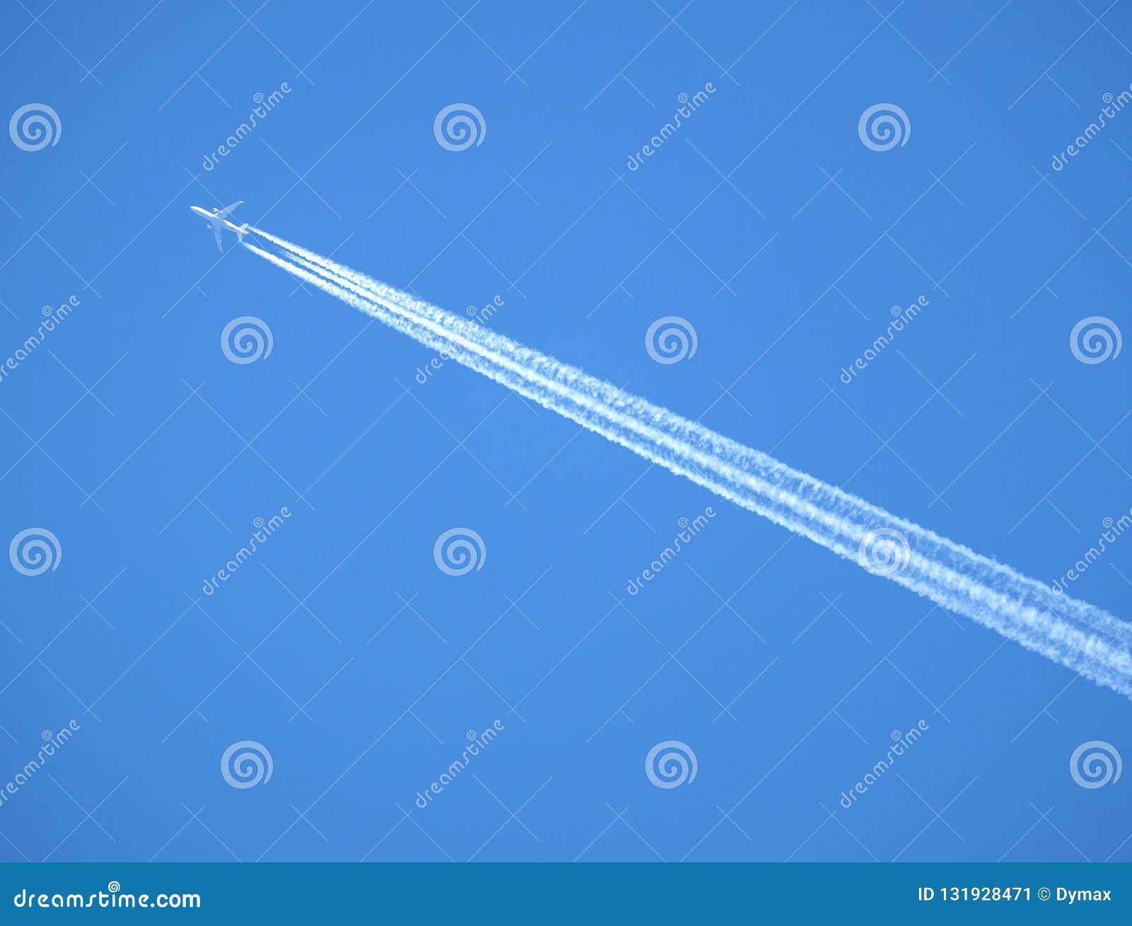 Pasażera samolotu odrzutowego latanie w jasnym niebieskim niebie, opuszcza białego ślad