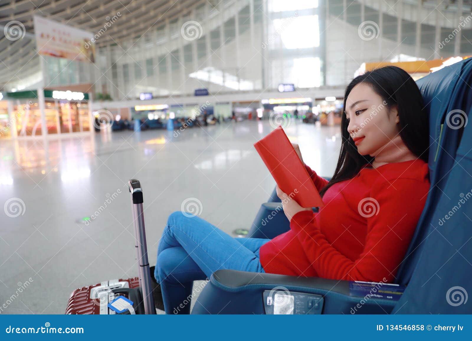 Pasażerska podróżnik kobieta w dworcu i czytającej książce