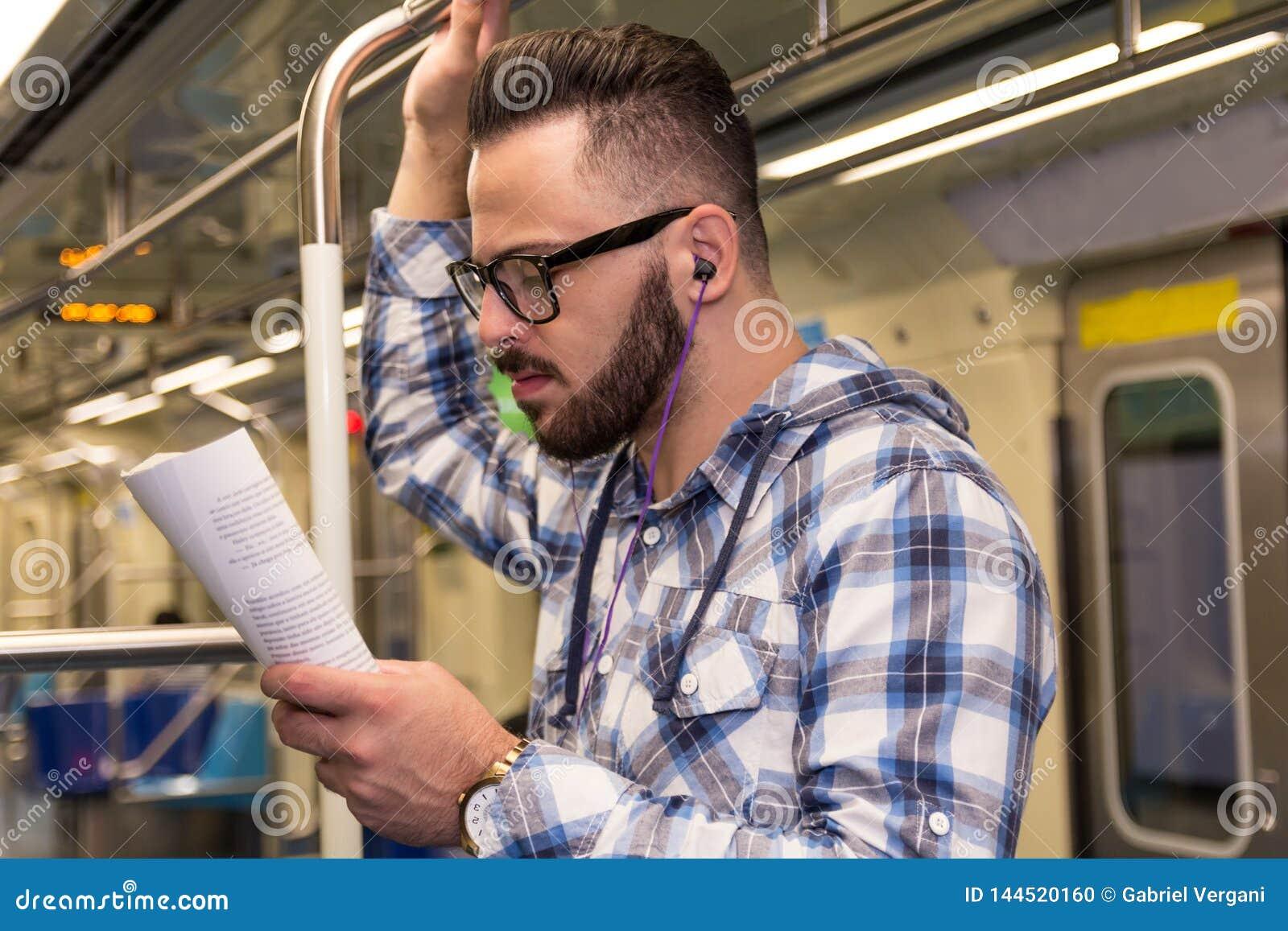Pasażerski facet jest oddanego student uniwersytetu czytelniczym książką podczas gdy jadący do domu metrem Pojęcie koncentracja,