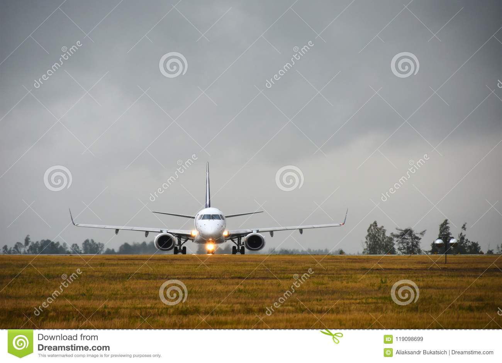 Pasażerski samolot z światłami dalej podróżuje pas startowy w lotniska polu w wieczór w deszczu, frontowy widok