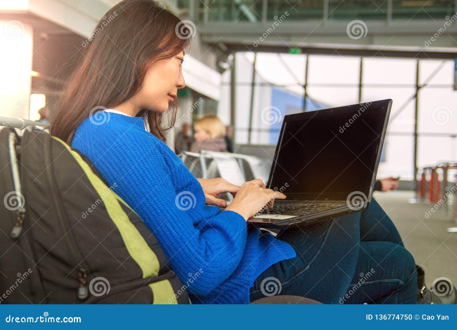 Pasajero femenino asiático joven que usa el ordenador portátil y el teléfono elegante mientras que se sienta en asiento en pasill
