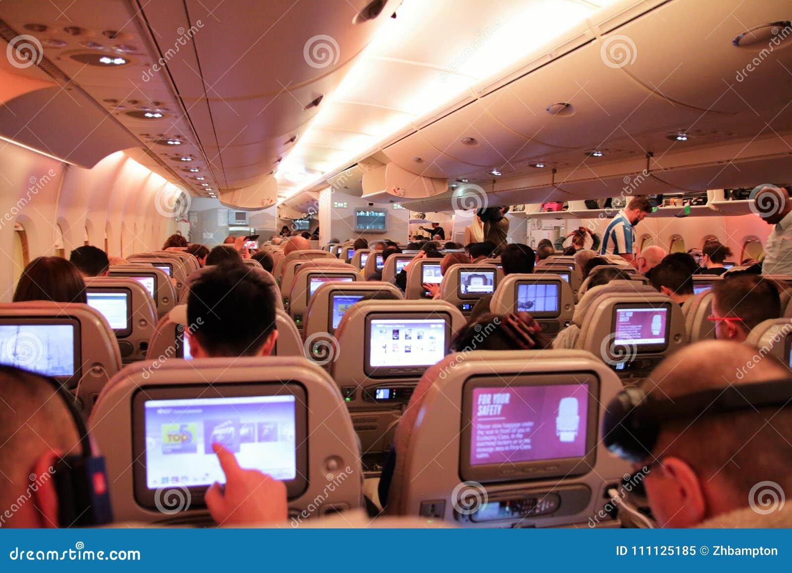 Pasajeros en un vuelo de la economía que muestra los asientos y las pantallas táctiles
