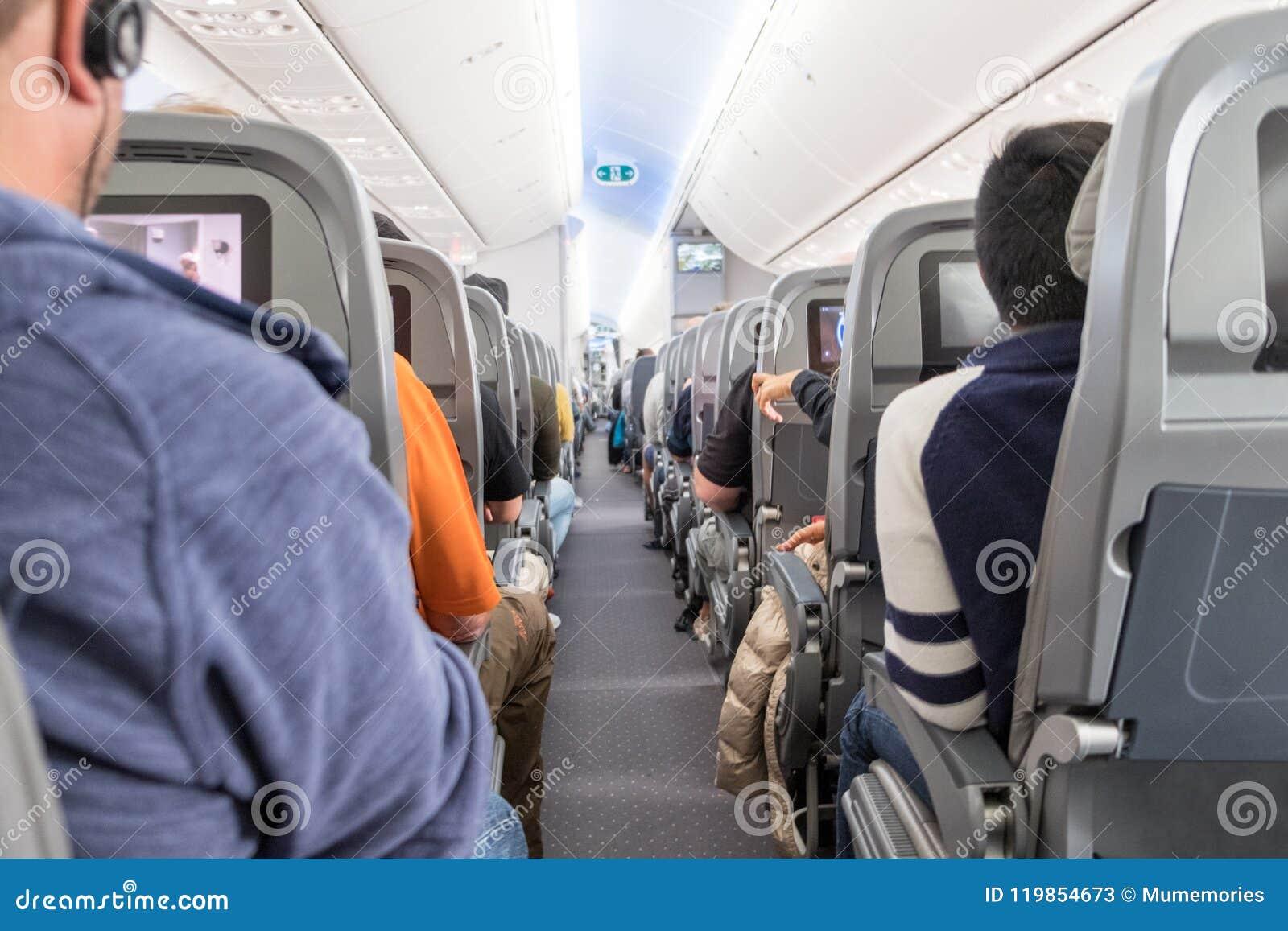 Pasajeros no identificados que se sientan en asientos en aeroplano
