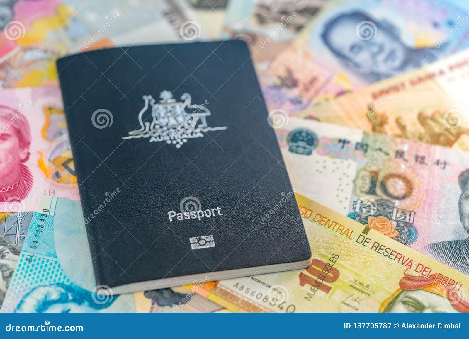 Pasaporte australiano del viaje que miente encima de los billetes de los países diferentes