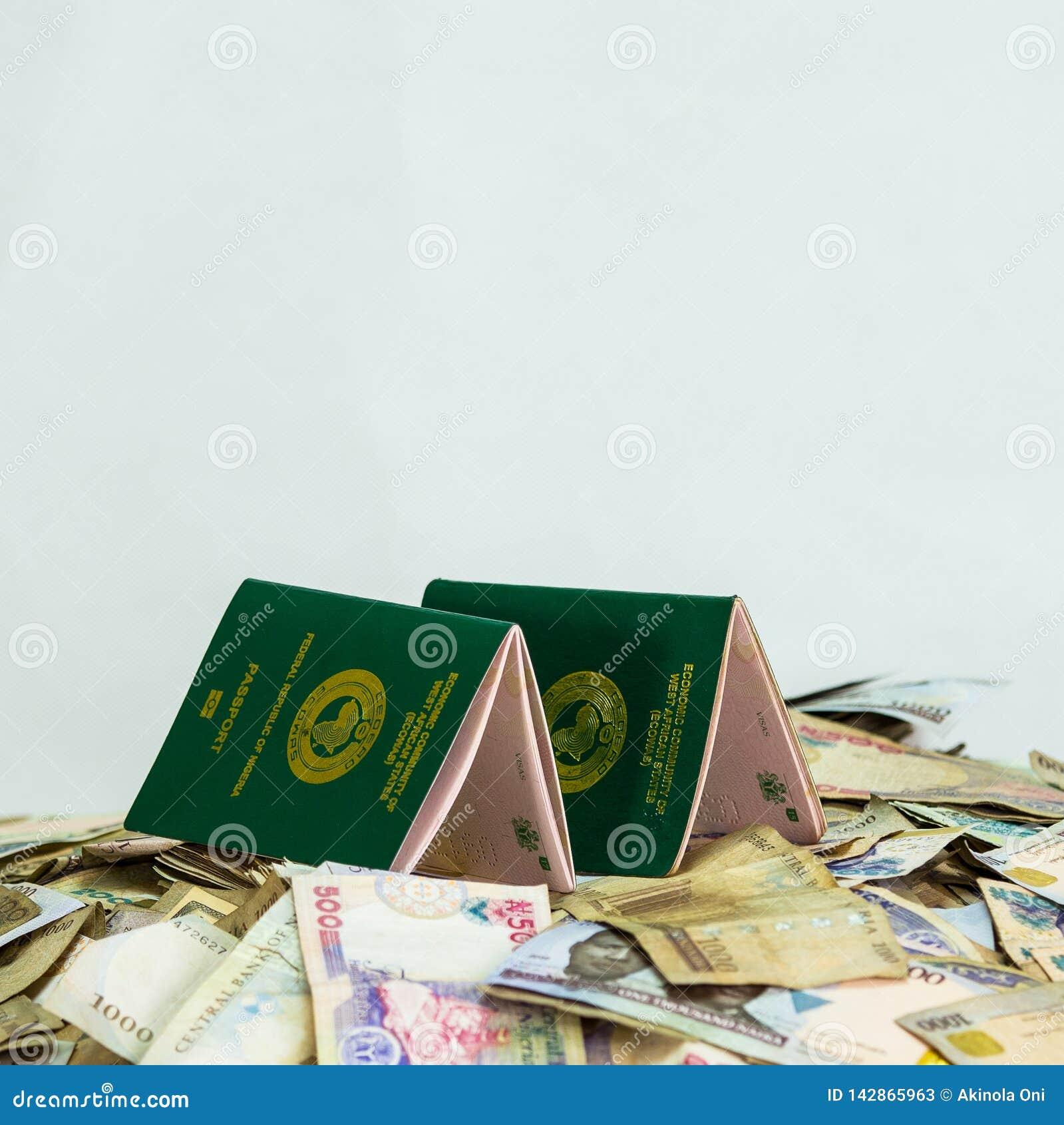 Pasaporte internacional múltiple de Ecowas Nigeria en un montón de las monedas locales del naira