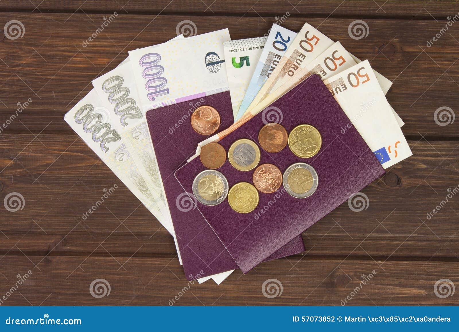 Pasaporte y dinero en la tabla de madera Billetes de banco, monedas válidas y billetes de banco EURO checos Migración ilegal para