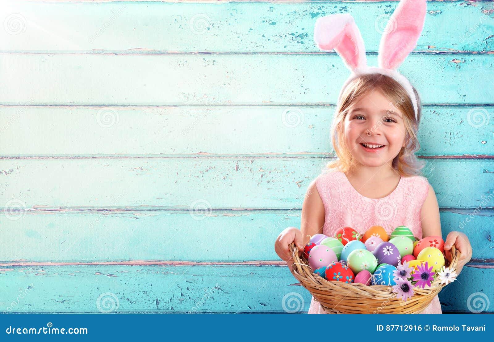 Pascua - niña con los huevos y Bunny Ears de la cesta