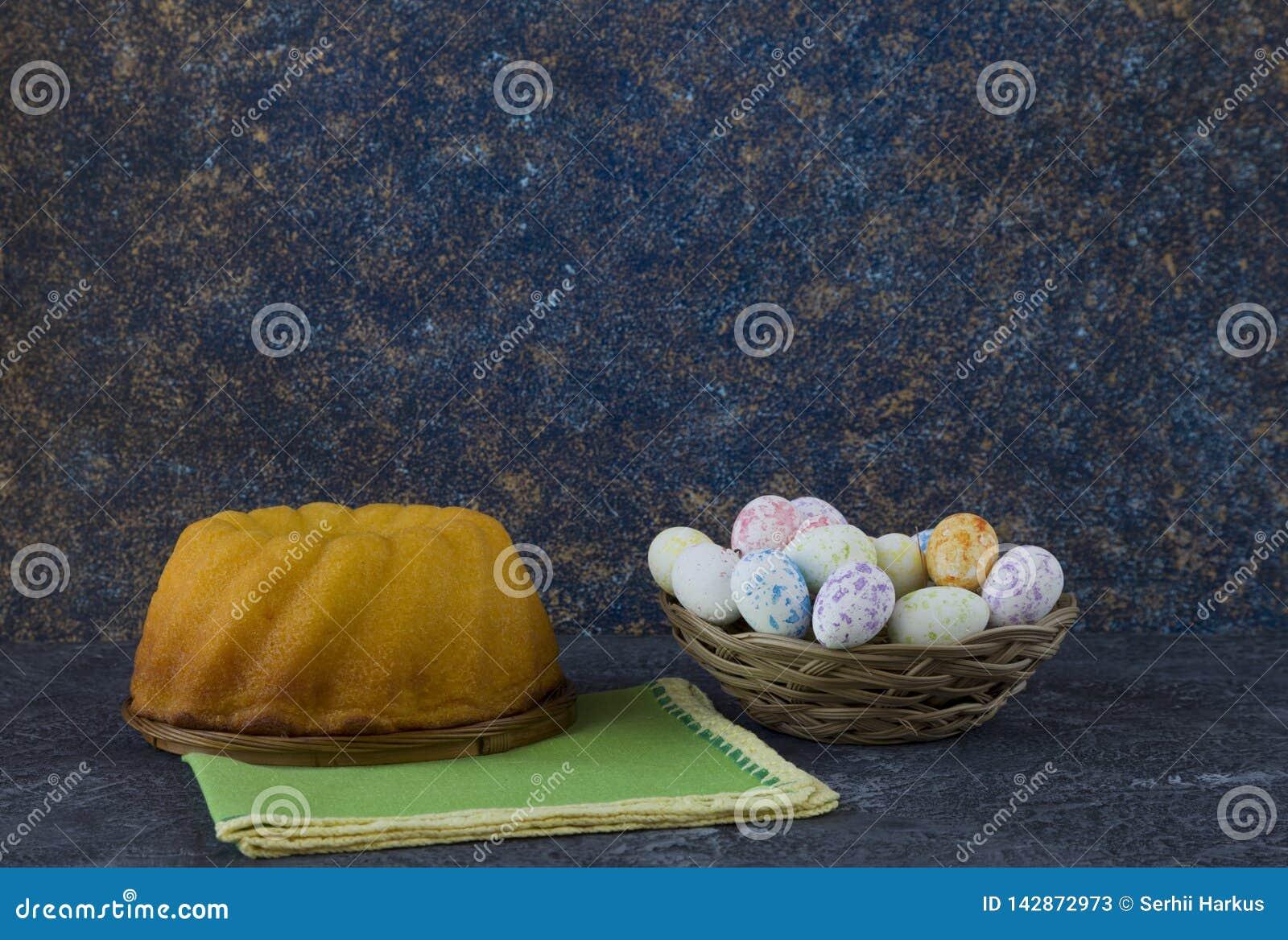 Pasen-brood en minipaaseieren in een kleine mand op donkere steenlijst