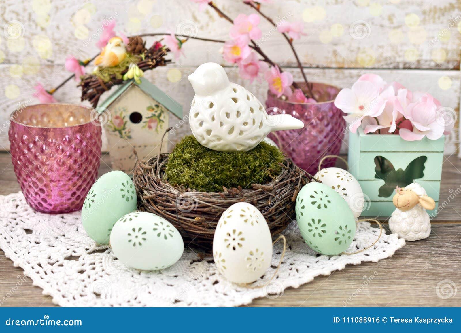 Pasen-decoratie met porseleinvogel in nest en eieren
