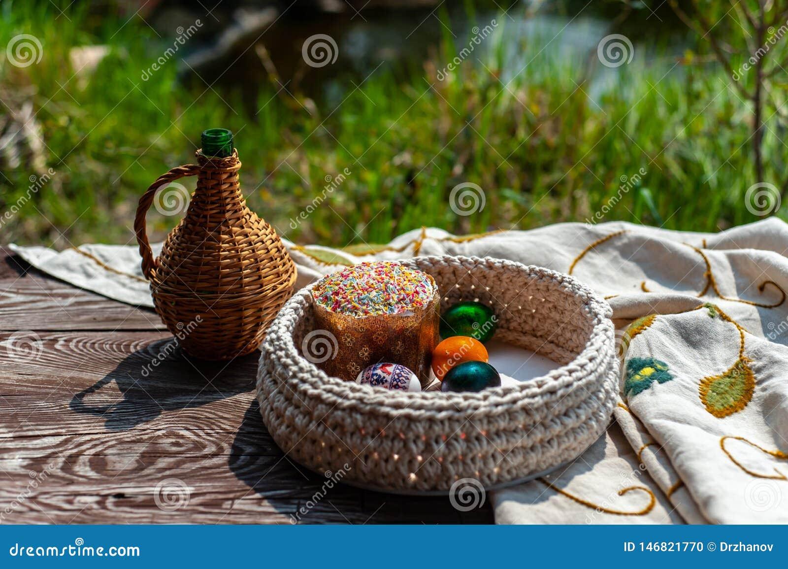 Pasen-het stilleven als kruik en gebreid pottle met gekleurde eierenbinnenkant blijft op de oude houten lijst met tafelkleed onde