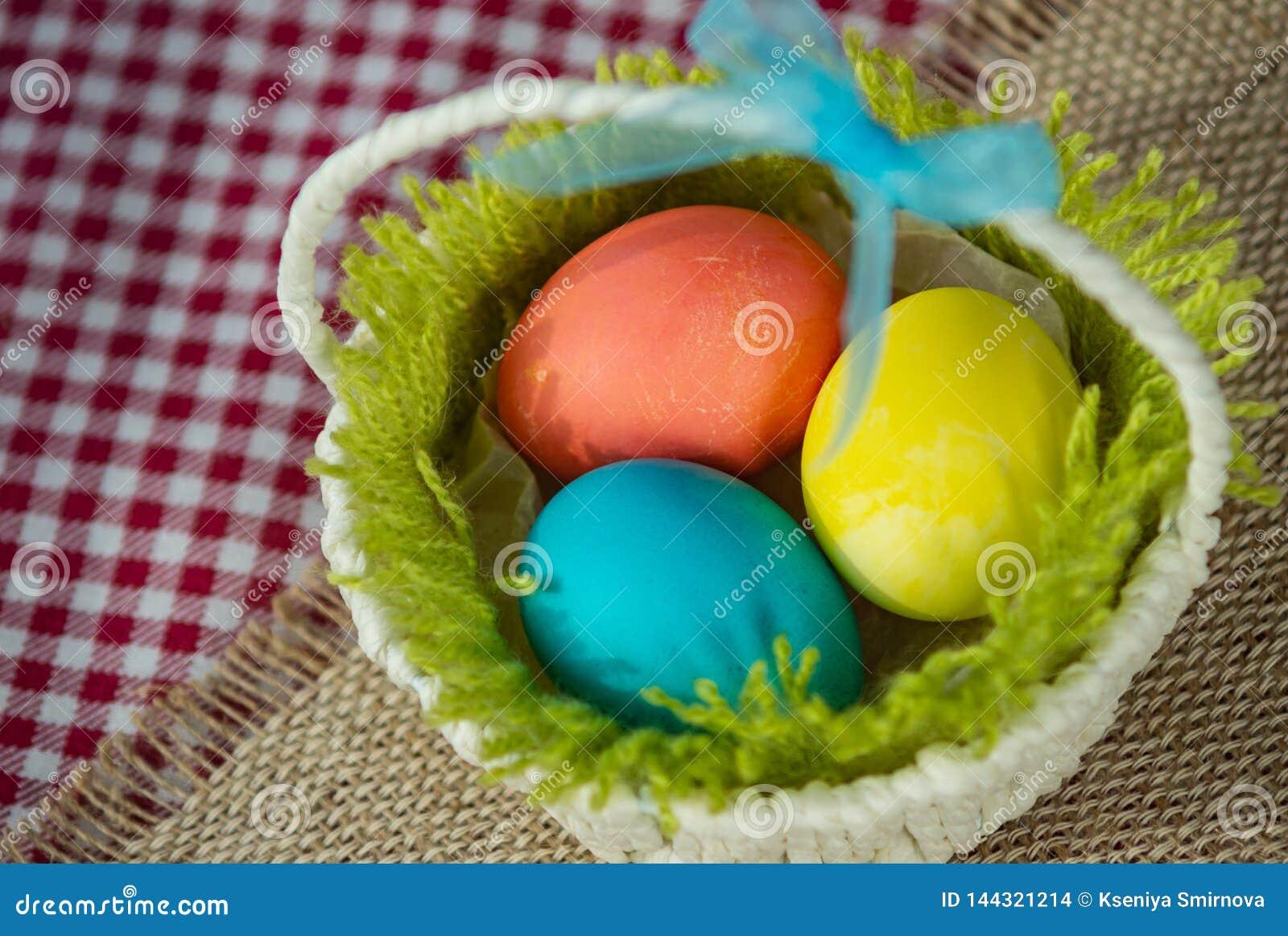 Pasen kleurde eieren in een mand op een canvasservet en een geruit tafelkleed