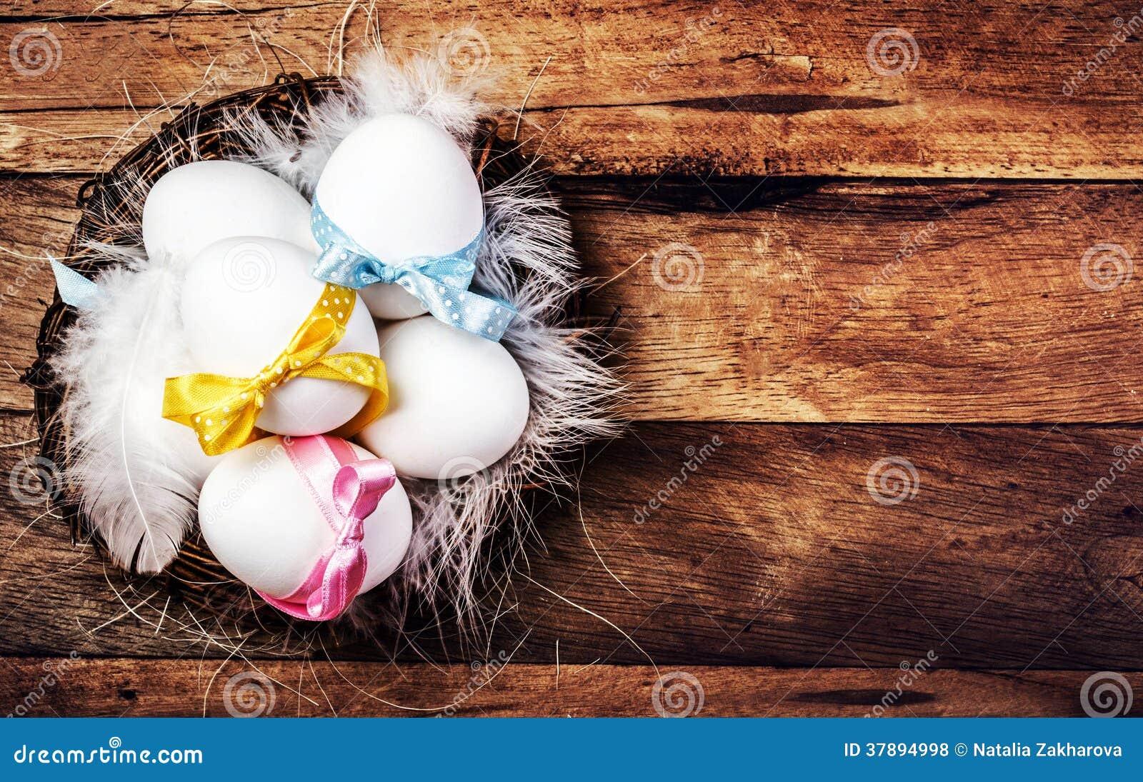 Pasen-nest met Eieren, linten en witte veren op houten bac