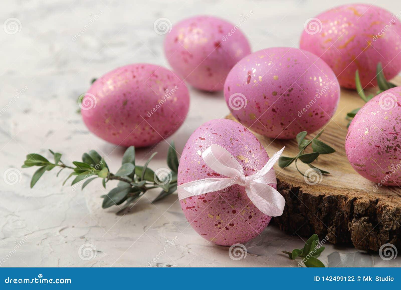 Pasen Roze paaseieren op een houten tribune op een lichte concrete achtergrond Gelukkige Pasen vakantie Close-up