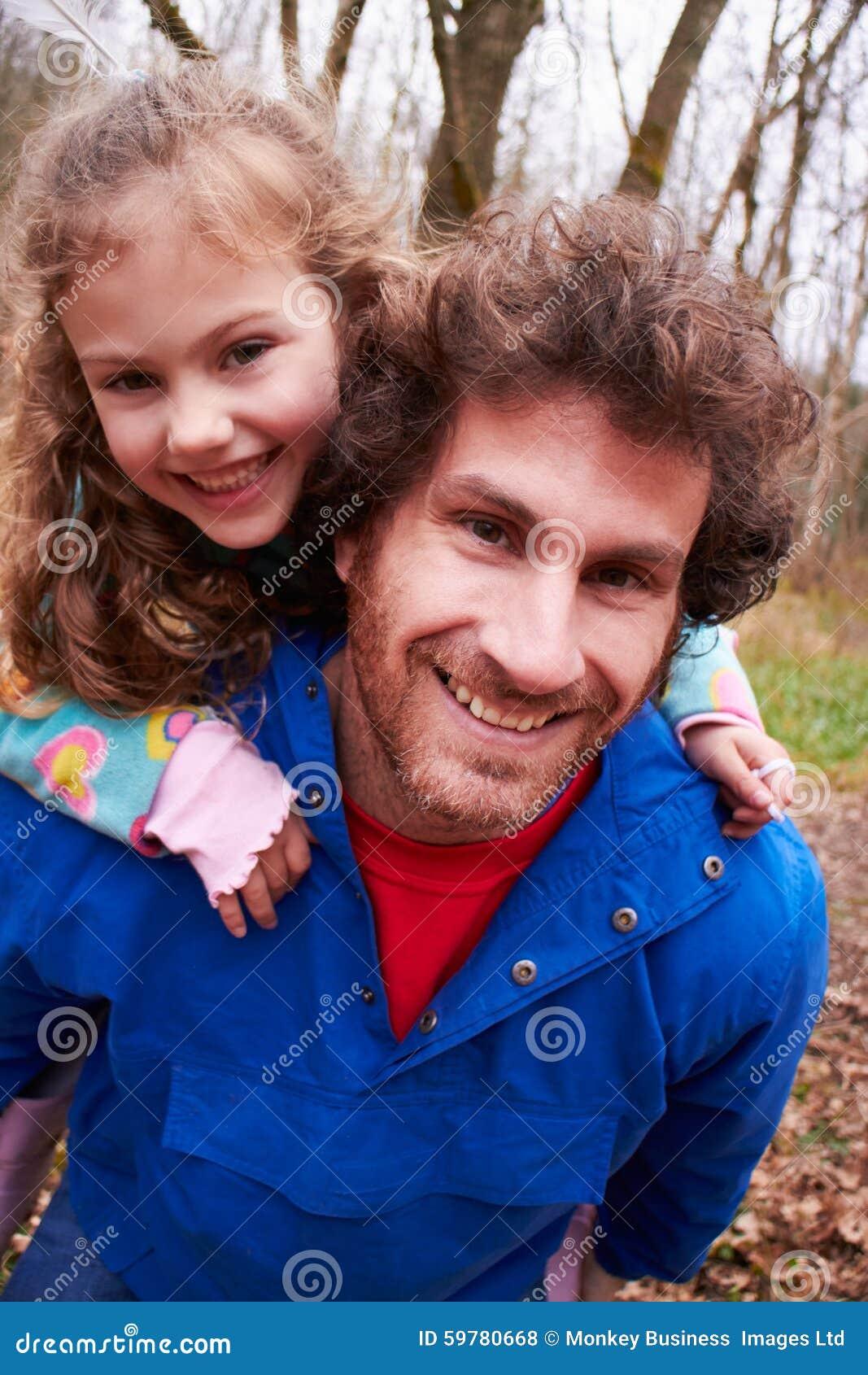 Paseo de Giving Daughter Piggyback del padre en paseo del campo