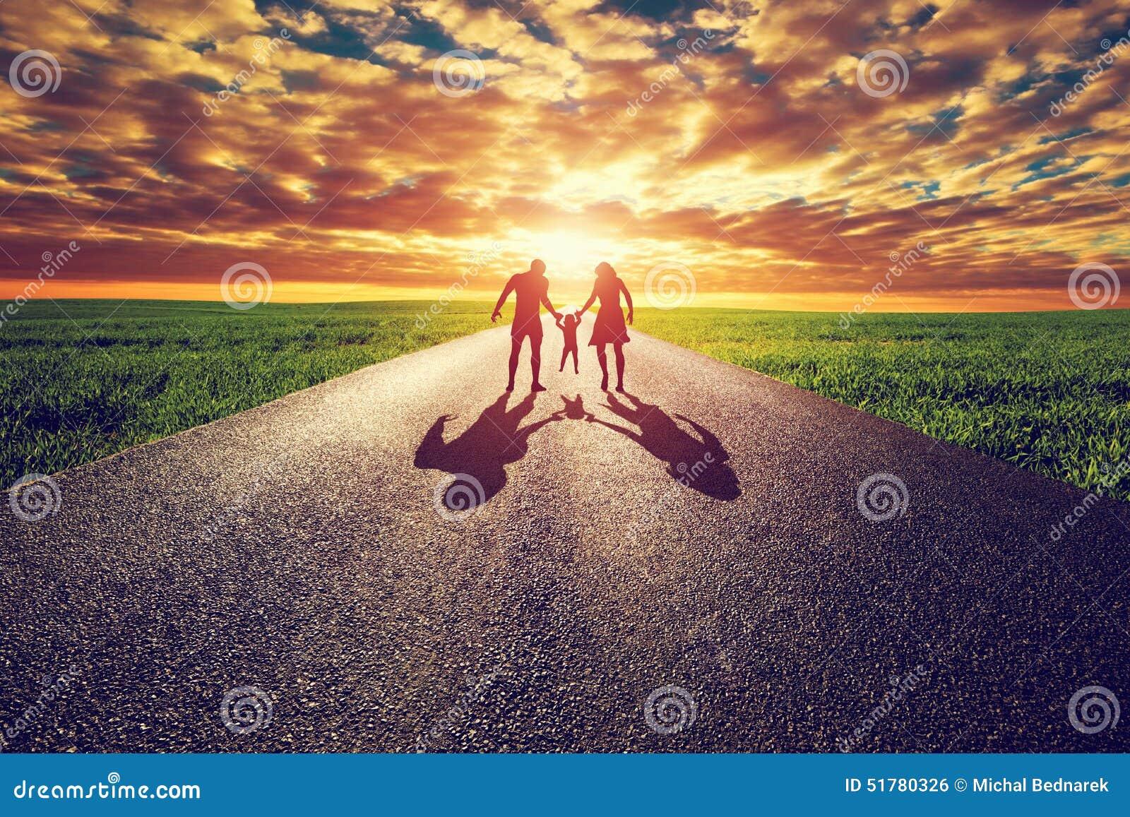 Paseo en el camino recto largo, manera de la familia hacia el sol de la puesta del sol