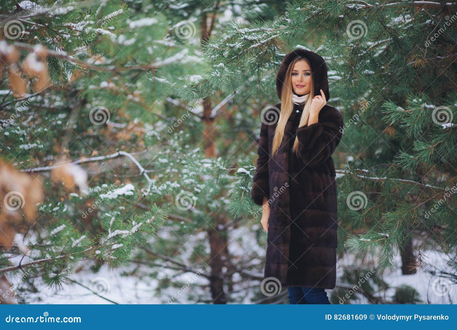 Paseo modelo joven de la muchacha en el bosque del invierno