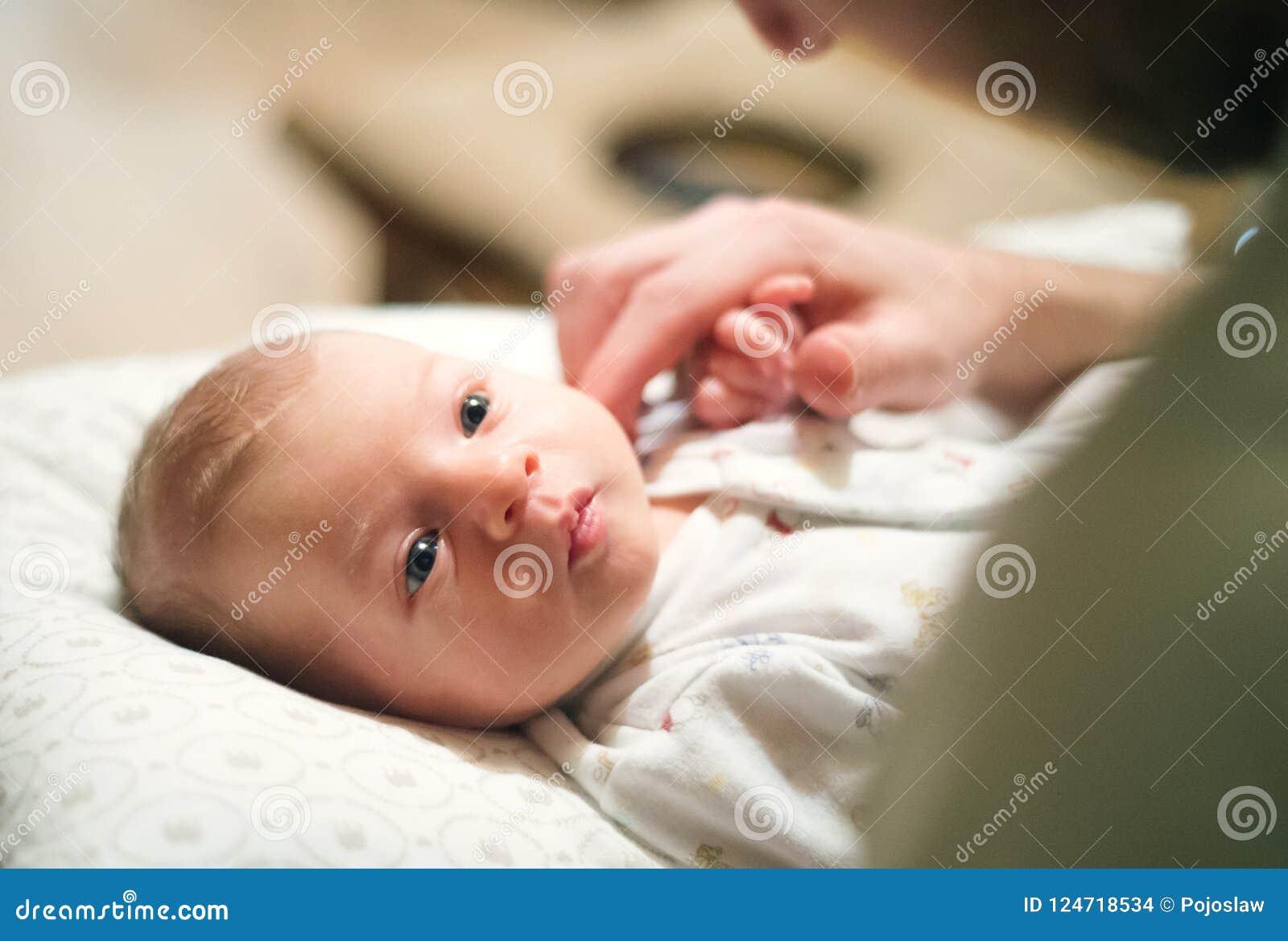 Pasgeboren baby die op bed, onherkenbare vader liggen die haar hoofd strijken