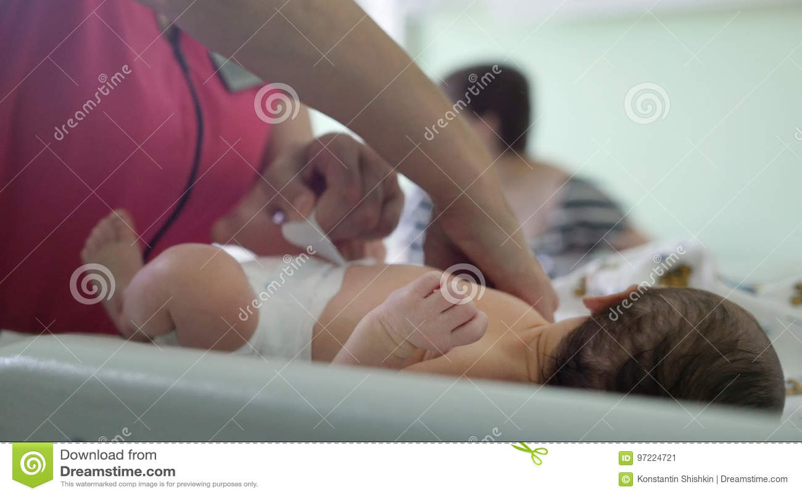 Pasgeboren baby in het moederschapsziekenhuis - de verpleegster wikkelt de zuigeling in