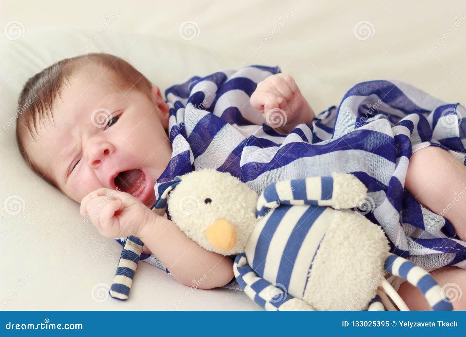 Pasgeboren baby met een gestreept sjaal en een stuk speelgoed, zachte nadrukachtergrond