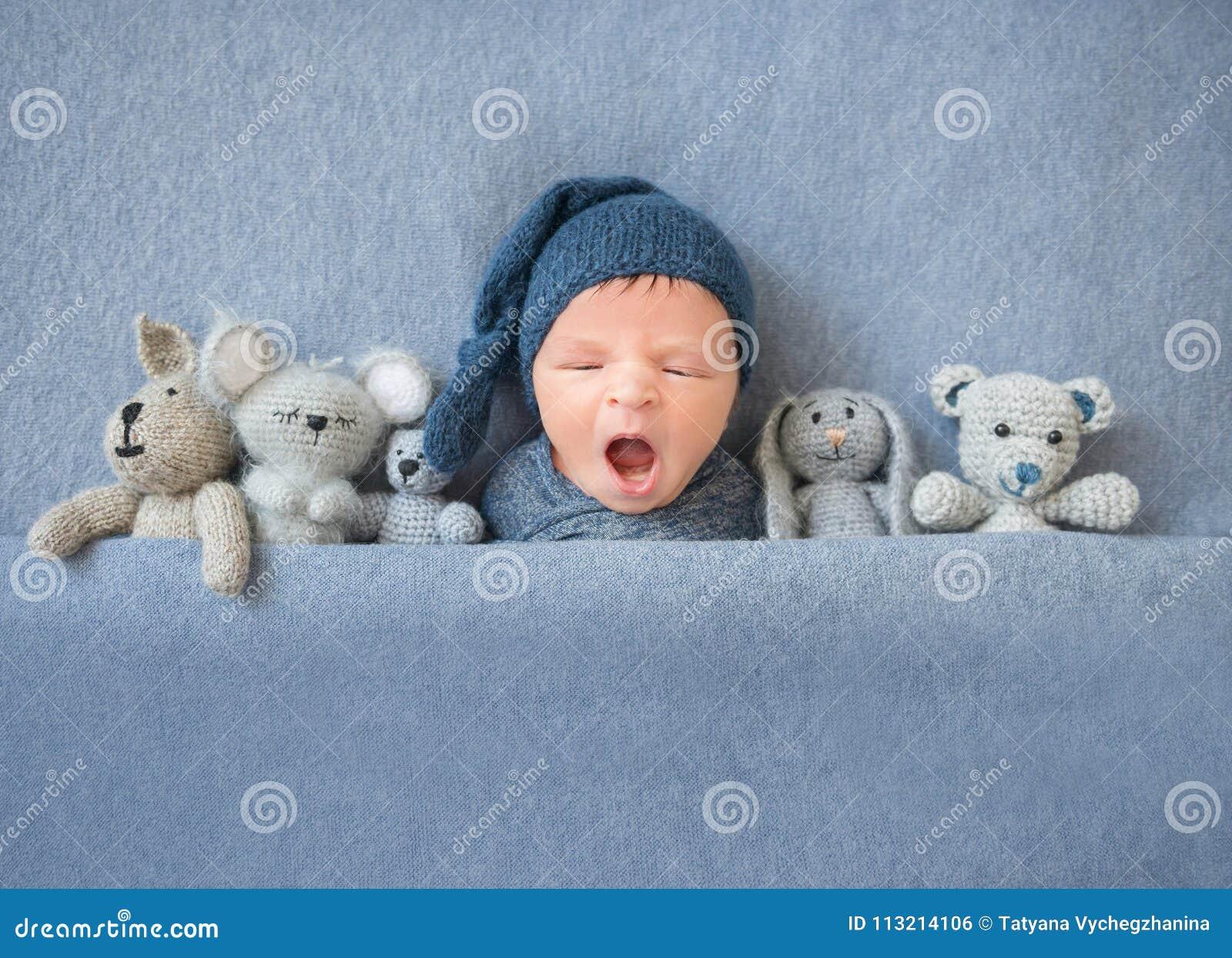 Pasgeboren babyjongen die en tussen pluchespeelgoed geeuwen liggen