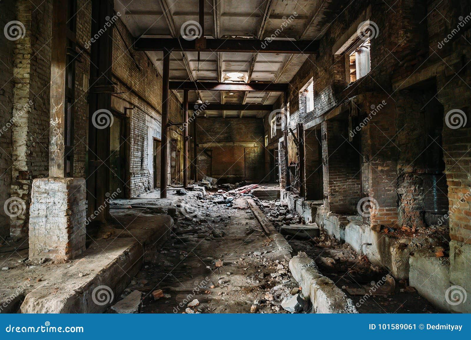 Pasillo asustadizo oscuro en la fábrica arruinada industrial abandonada del ladrillo, interior espeluznante, perspectiva