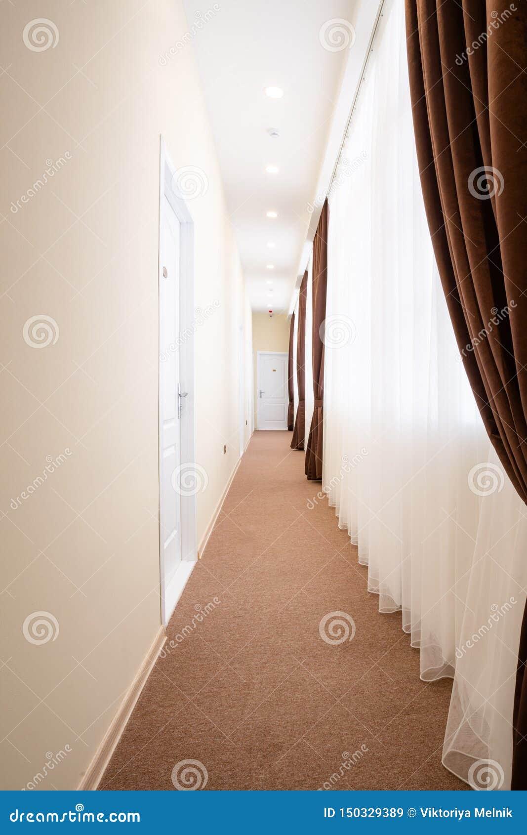 Pasillo brillante con las puertas blancas, la alfombra marrón, las cortinas blancas de Tulle y las cortinas marrones