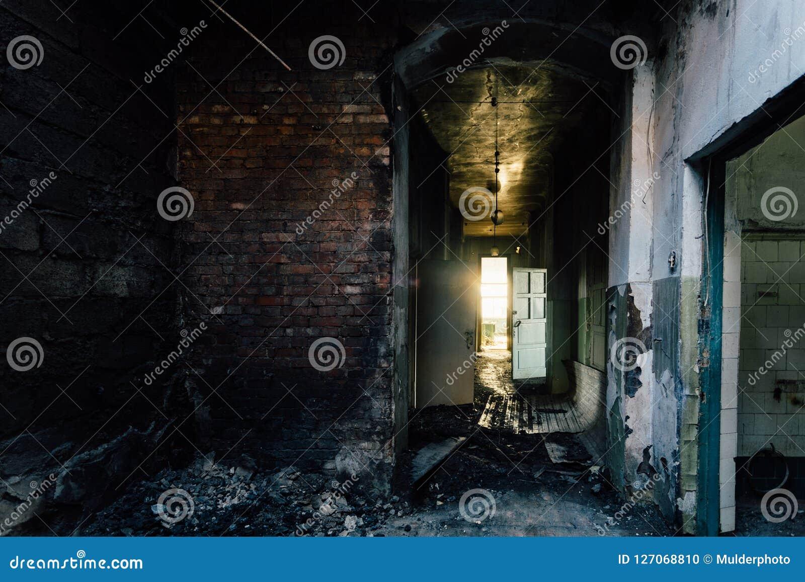Pasillo siniestro y espeluznante del hospital abandonado después del fuego Techo en hollín negro