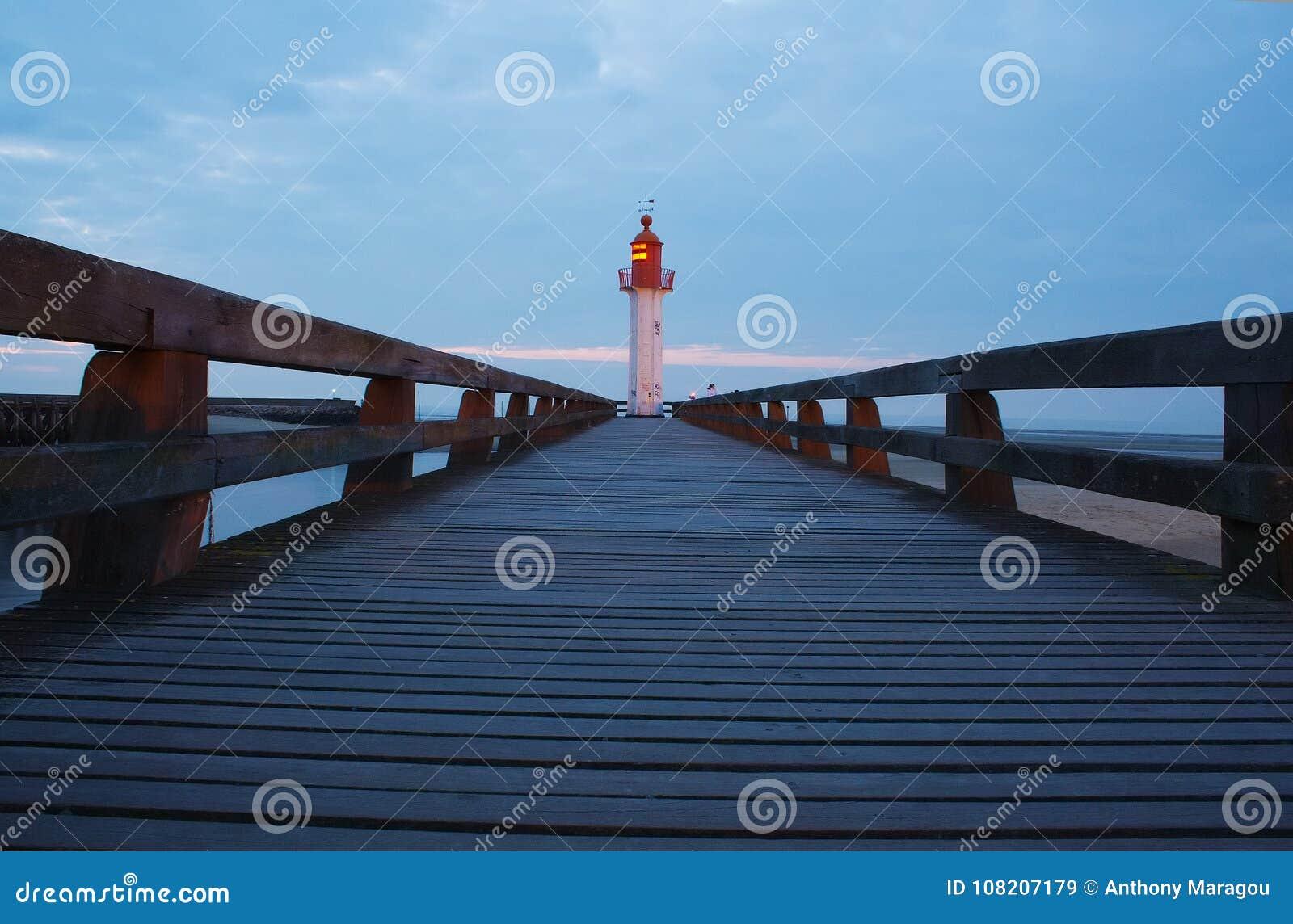 Passage couvert et phare au coucher du soleil