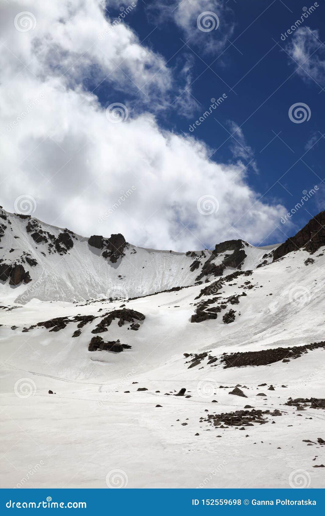 Passage de montagne ensoleillé avec la corniche de neige et le ciel nuageux bleu