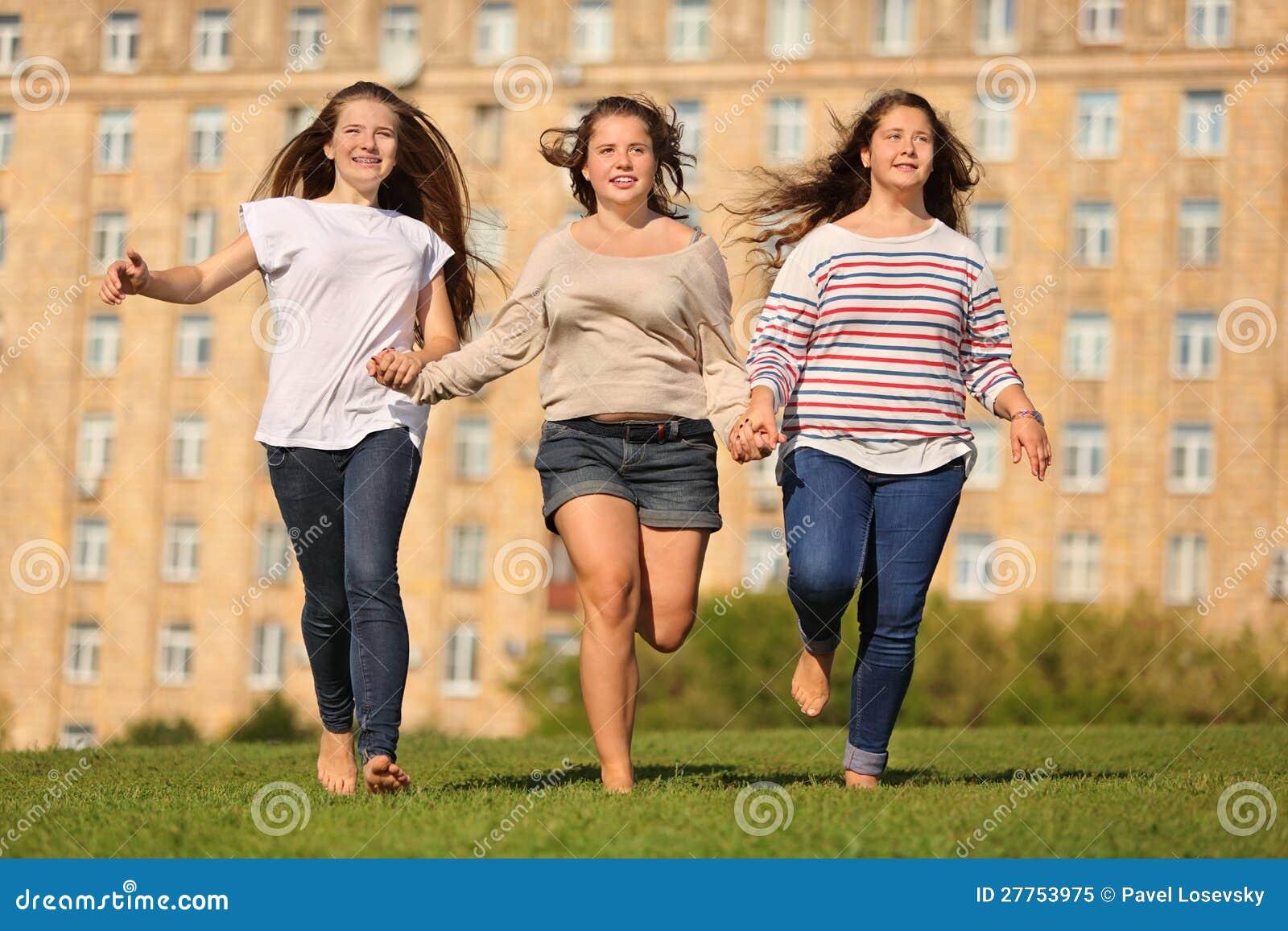 Passage de sourire de trois filles aux mains d herbe et de prise