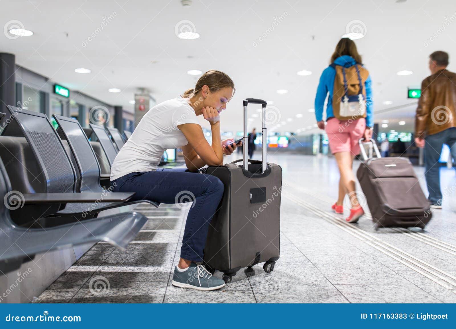 Passageiro fêmea novo no aeroporto, usando seu tablet pc