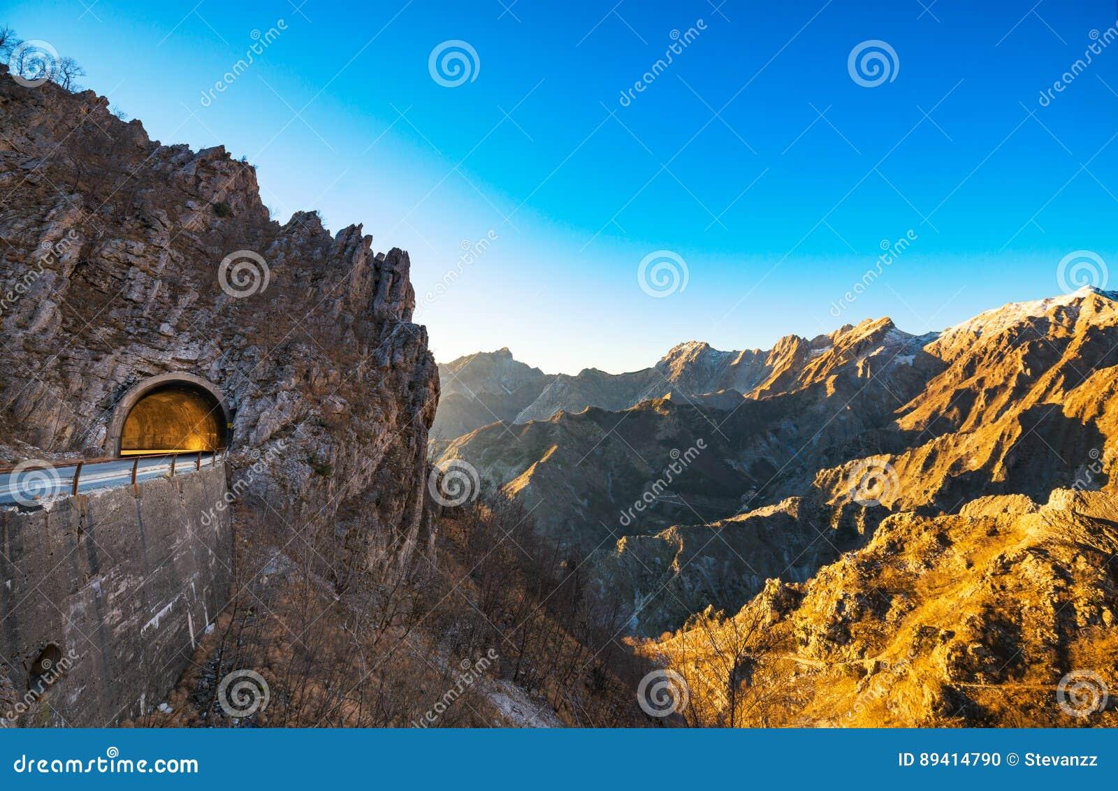 Passagem da estrada da montanha de Alpi Apuane e opinião do túnel no por do sol Carrar