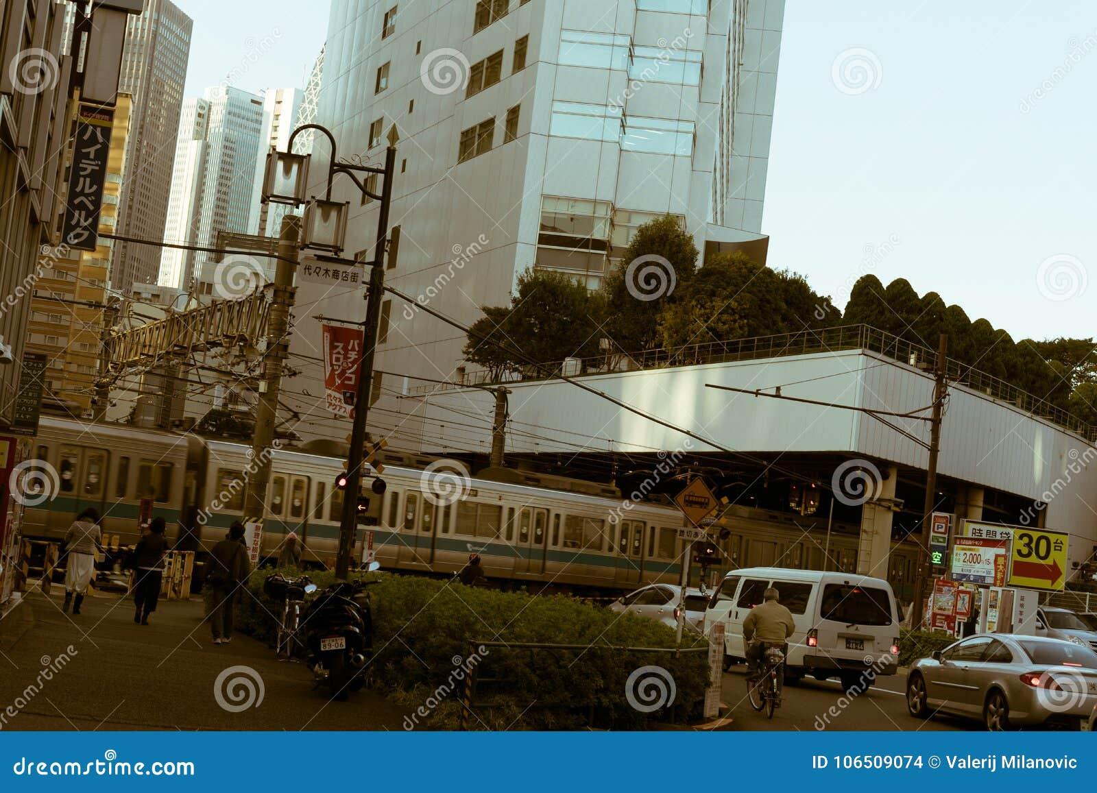 Passagem de nível com o trem do trem que passa completamente no Tóquio, Japão