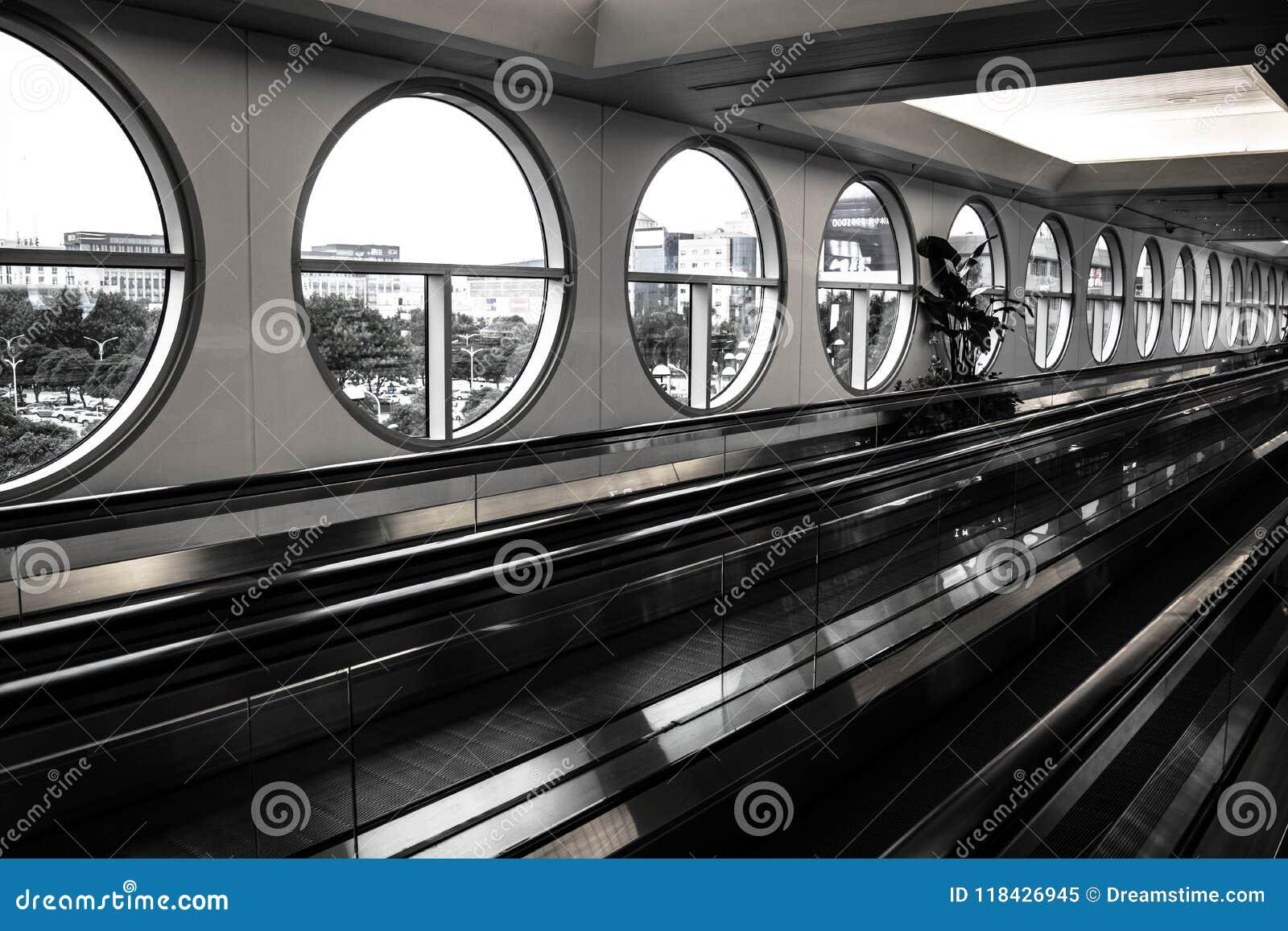 Passagem movente do aeroporto com as janelas circulares em preto e branco