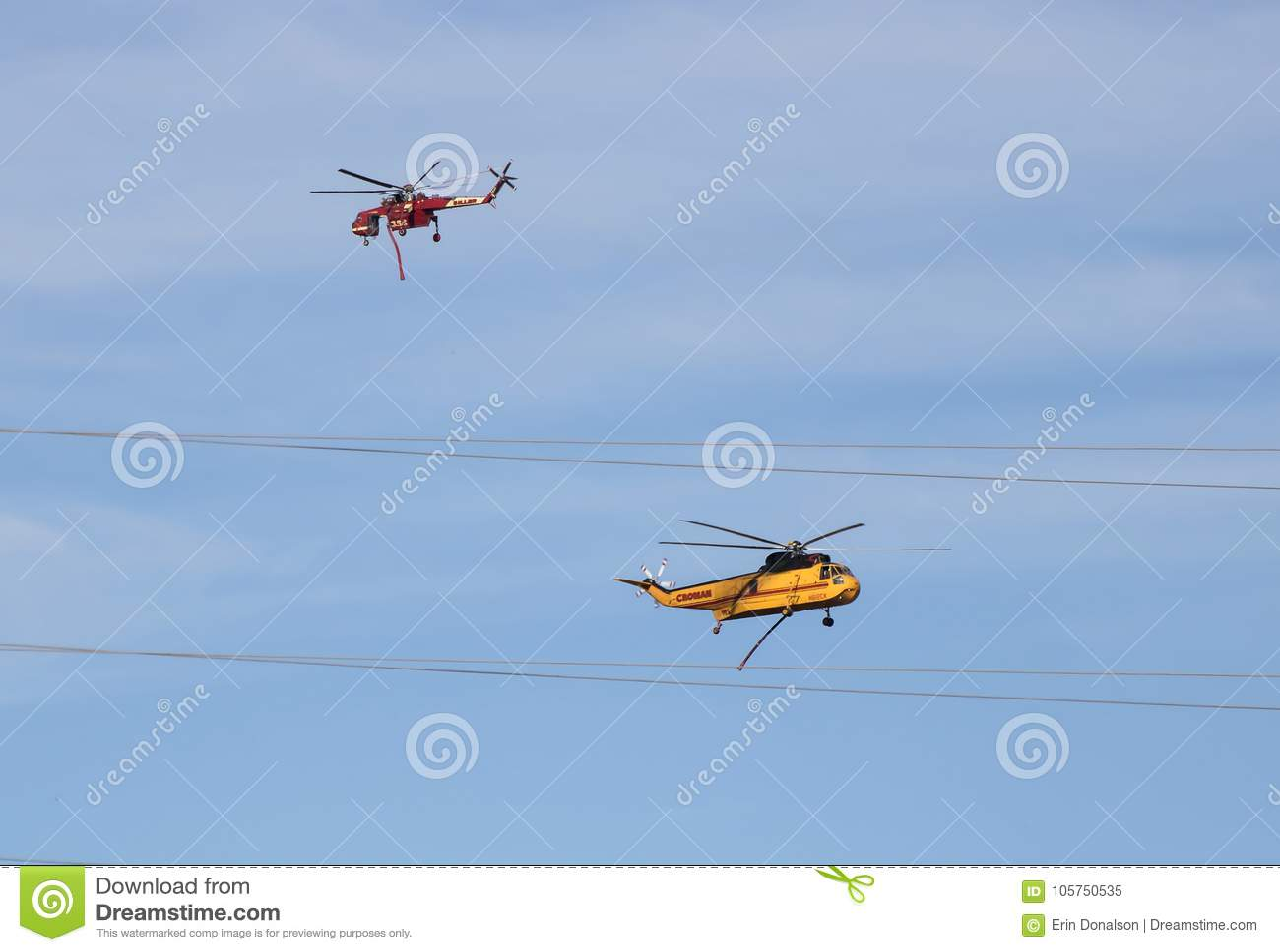 Passagem vermelha e amarela dos helicópteros do fogo na luta do fogo