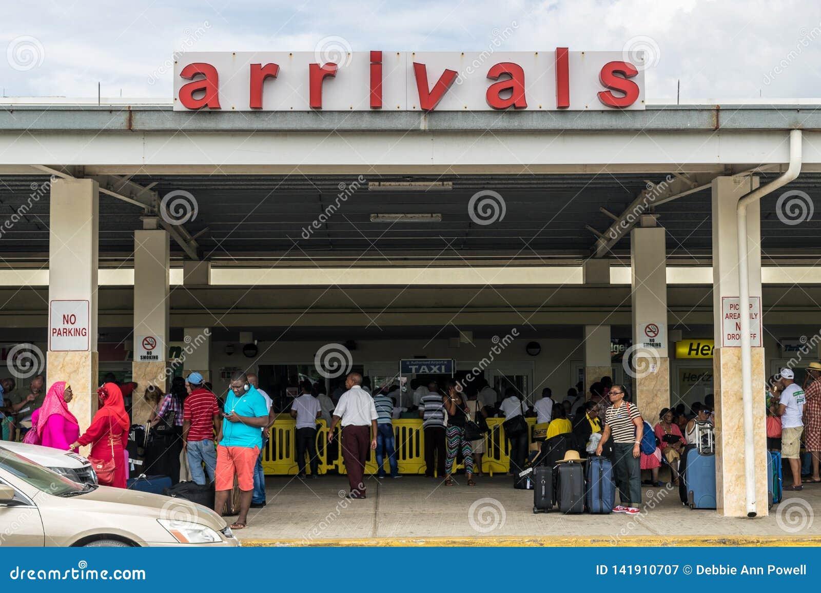 Passagerare på ankomster i Sangster den internationella flygplatsen i Montego Bay, Jamaica