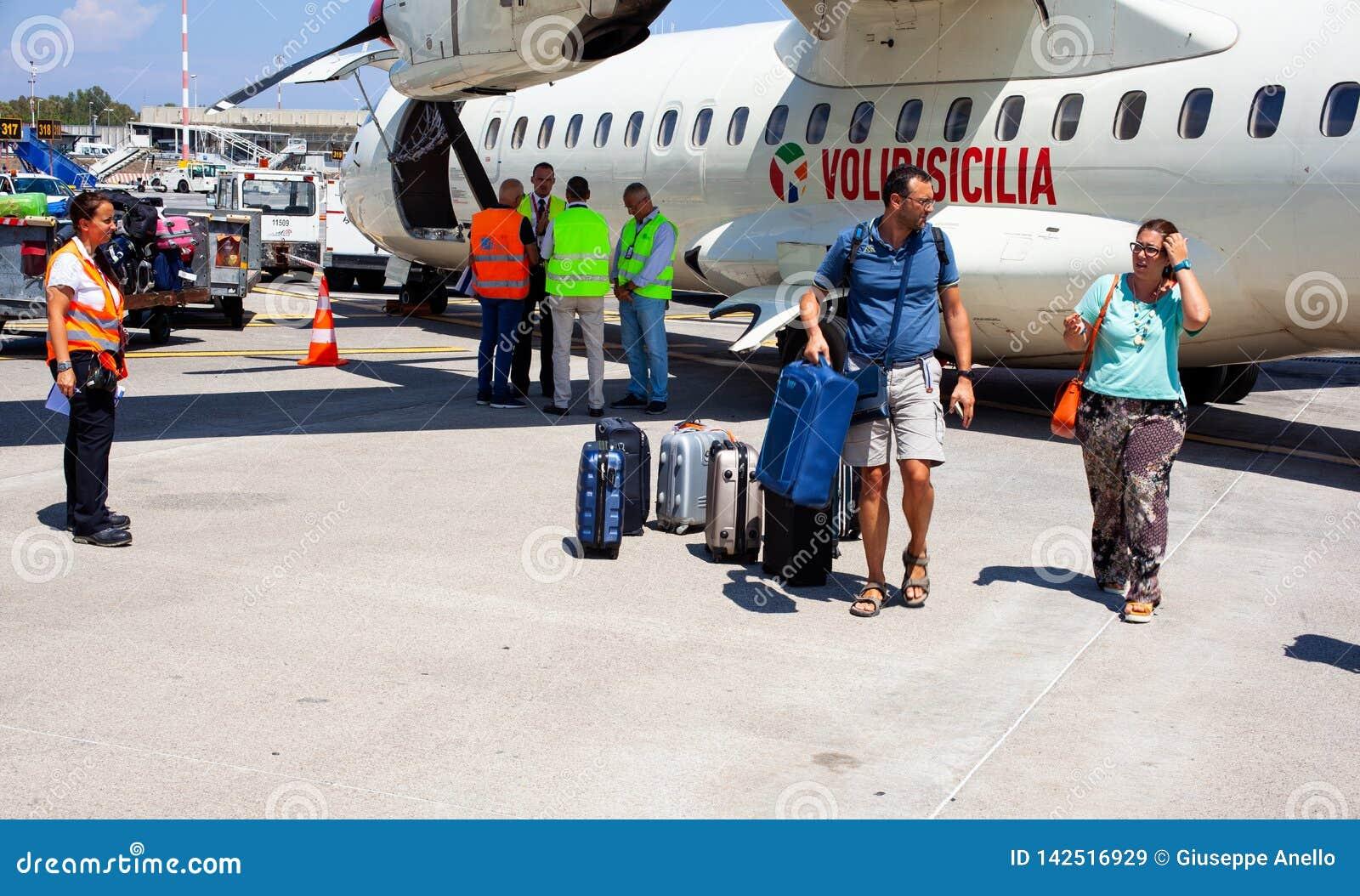 Passagiere mit Gepäck nahe bei dem Flugzeug