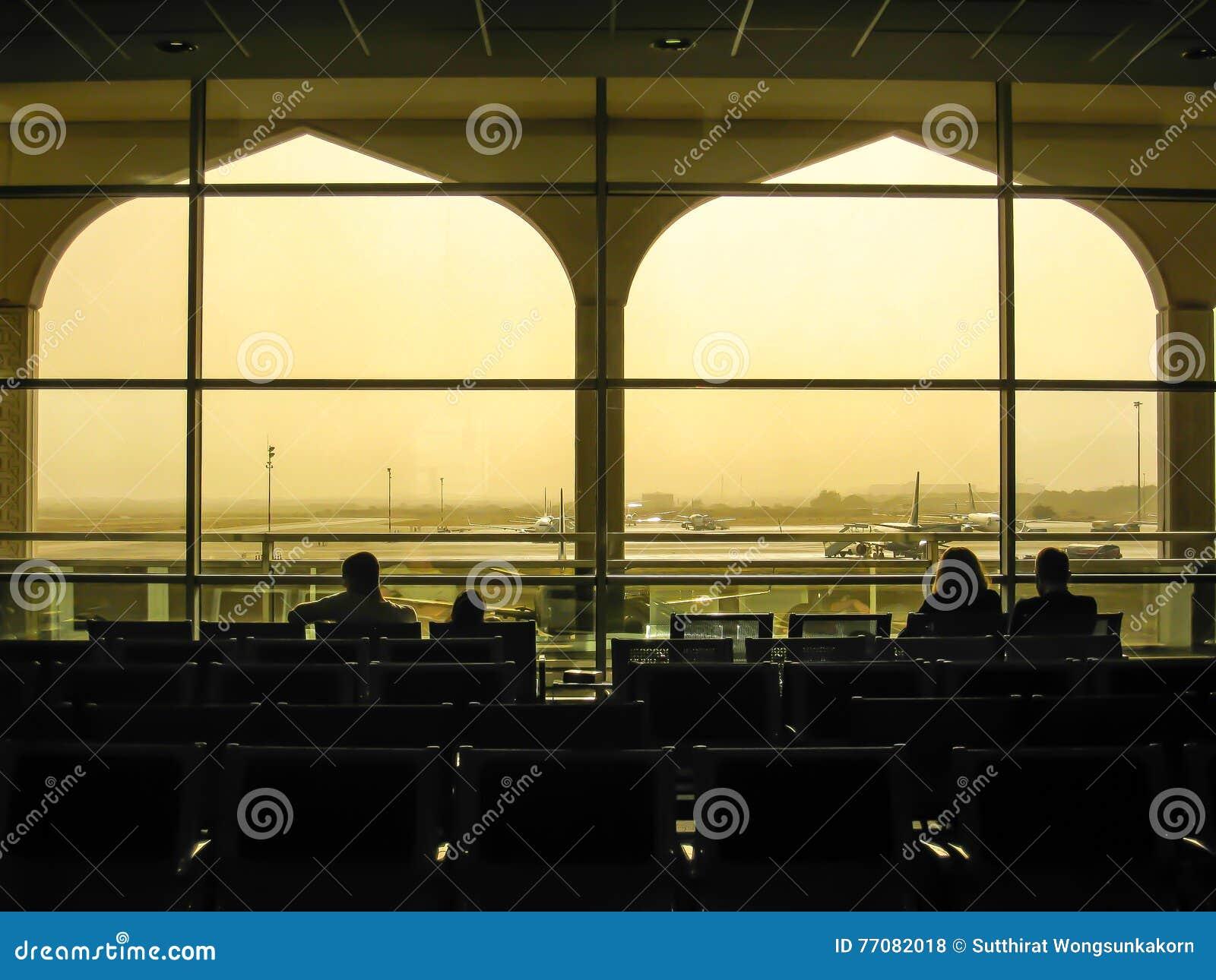 Passagiers bij Muscateldruifluchthaven in silhouet, Oman