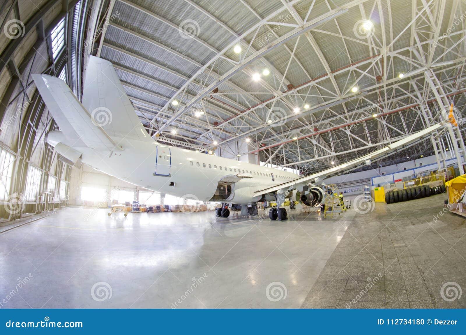 Passagiersvliegtuig op onderhoud van motor, fuselage en op hulpkrachteenheid controleer reparatie in luchthavenhangaar Vliegtuige